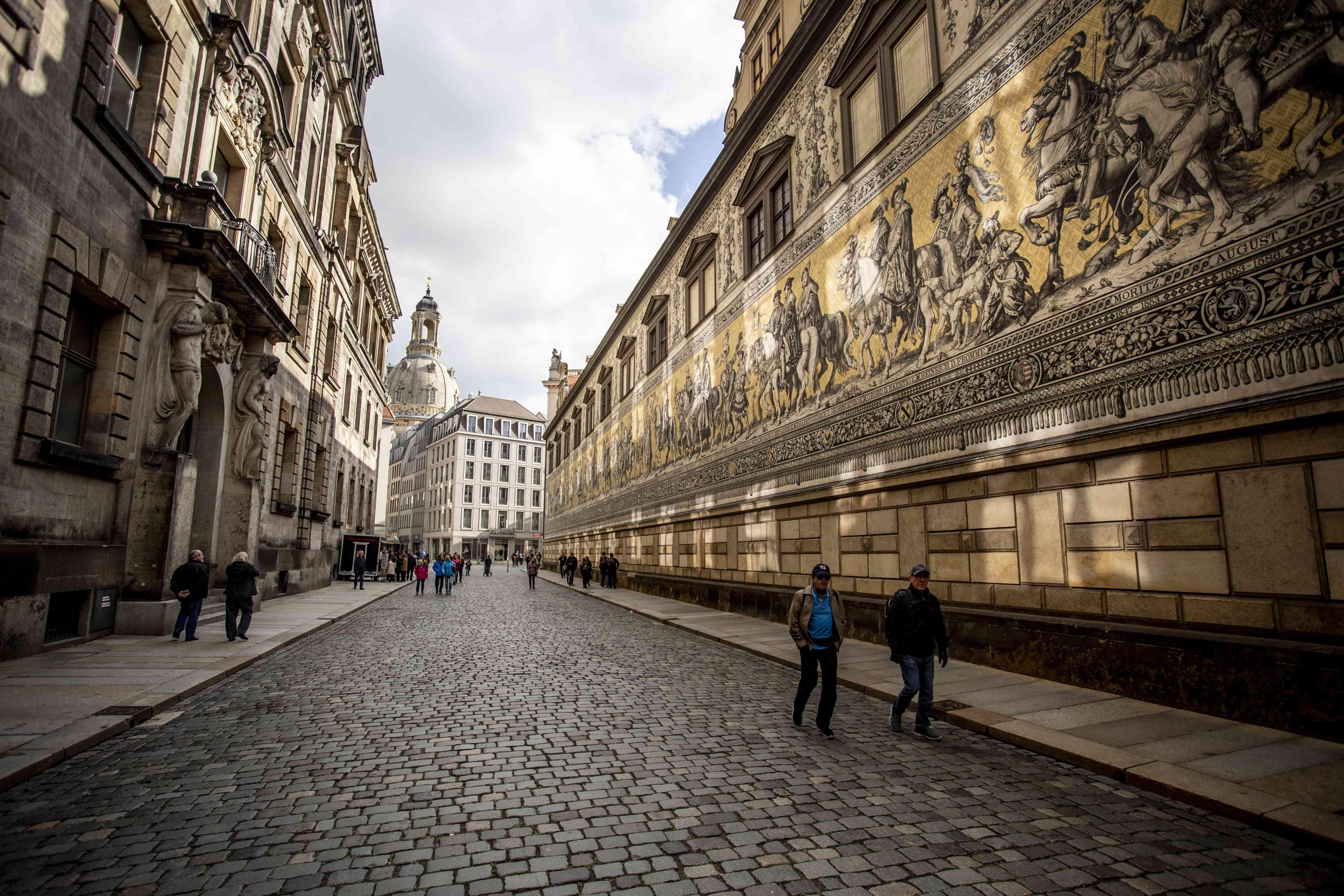 Gente caminando junto al largo mural de la Procesión de los Príncipes