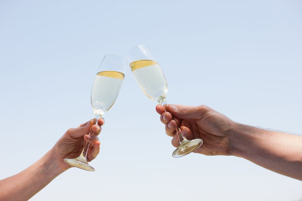 Two people toasting champagne flutes