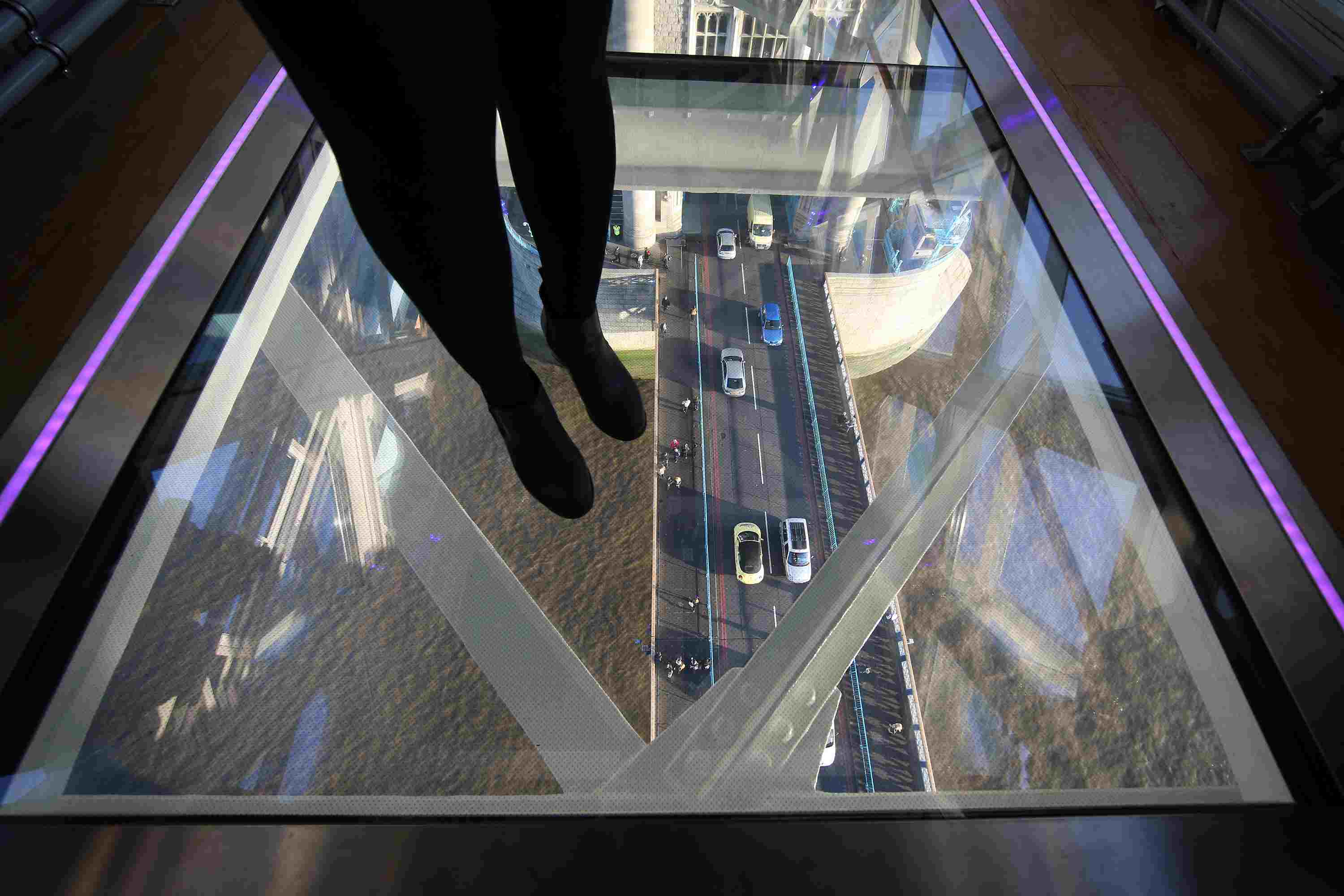 A visitor crosses Tower Bridge's glass walkway in London, England.