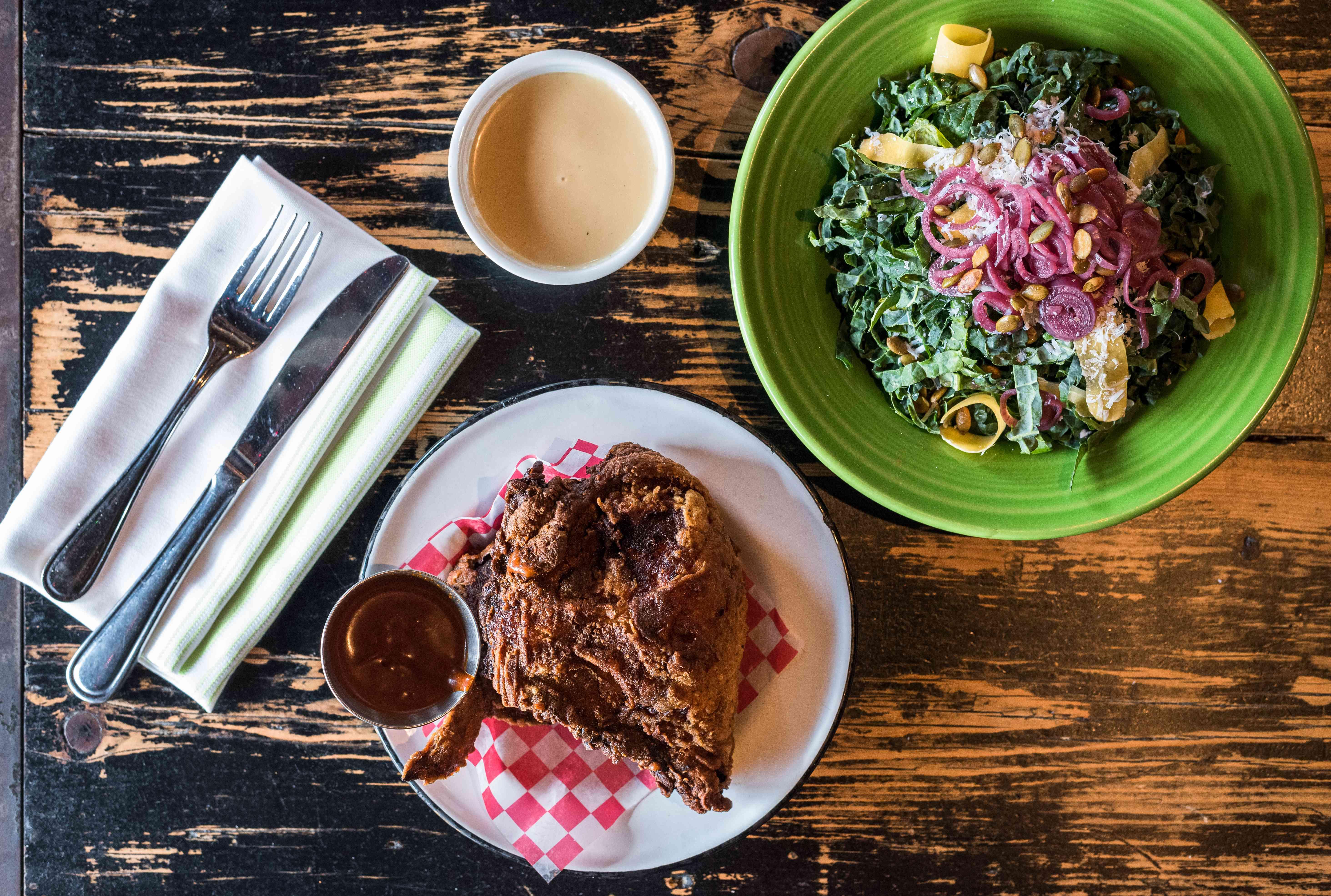 Plato de pollo frito y un plato de ensalada de Leon's Oyster SHop
