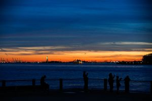 BROOKLYN, NY - APRIL 09: The Statue of Liberty stands against a spring sunset photographed from Brooklyn Bridge parkon April 09, 2017 in Brooklyn, New York.