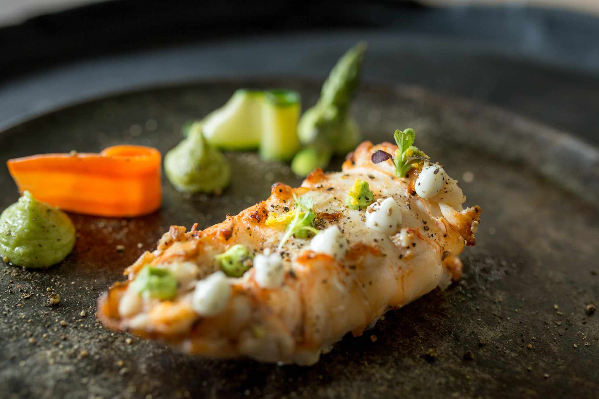 Shelled lobster tail with garnishes on a dark plate