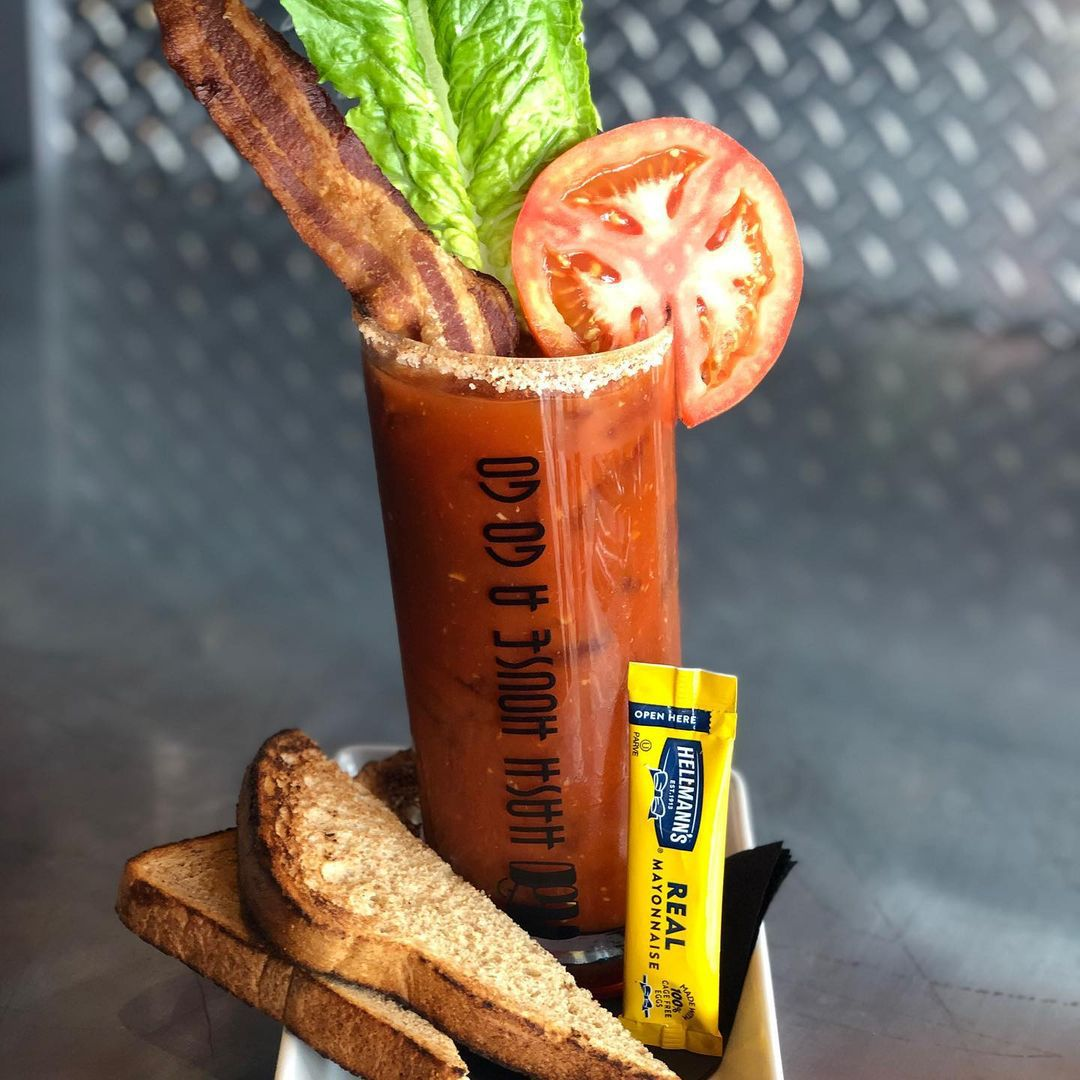 Bloody Mary garnished with strip of bacon, tomato slice, and lettuch leaf. the drink is on a place with two pieces of toast