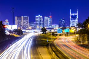 Long exposure of a Nashville highway at night with the skyline in the background