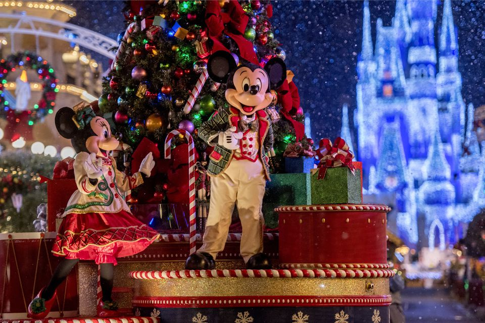 mickey and minnie mouse aboard a holiday float in christmas parade at disneys magic kingdom