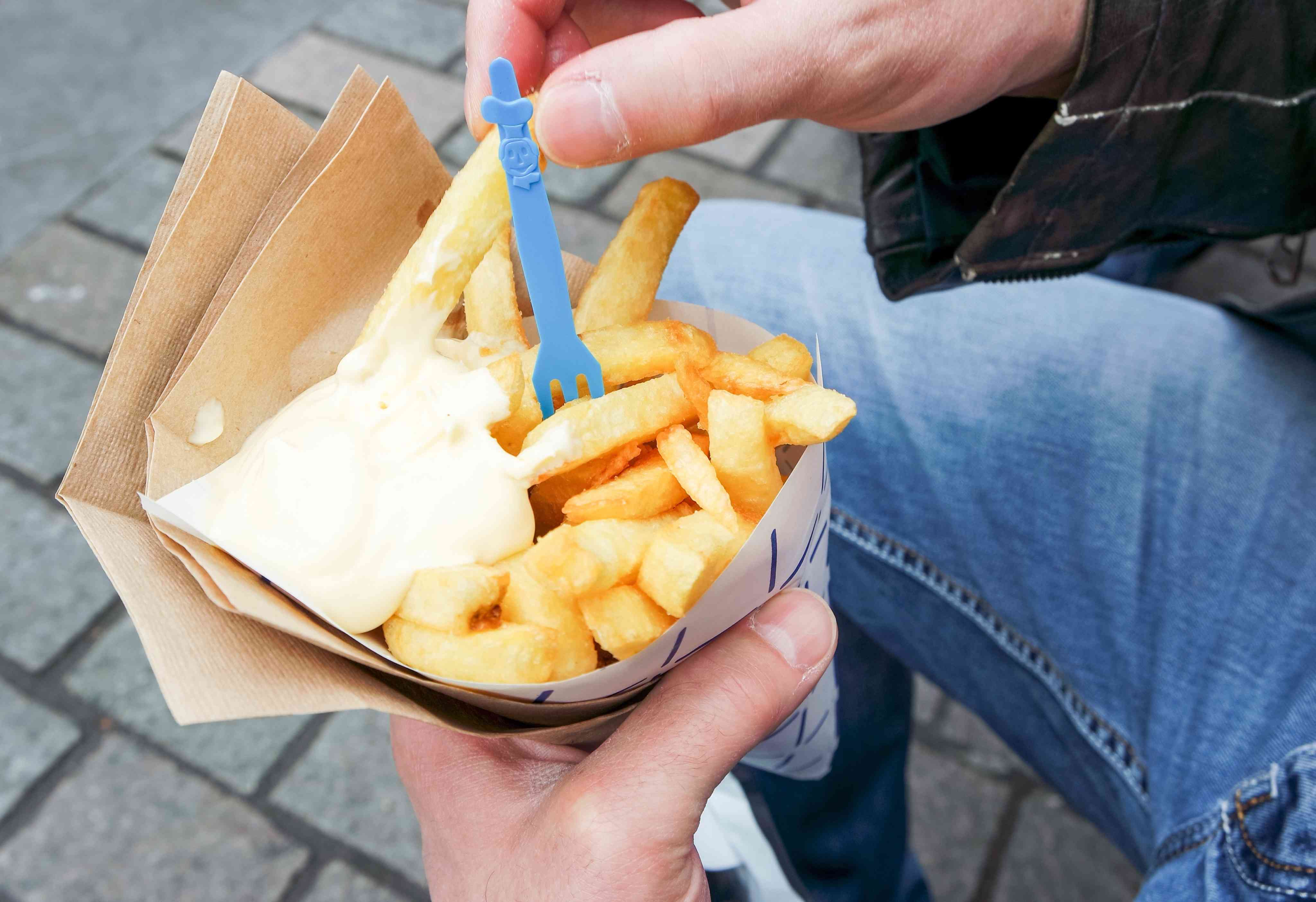 Person Holding French Fries Over Walkway