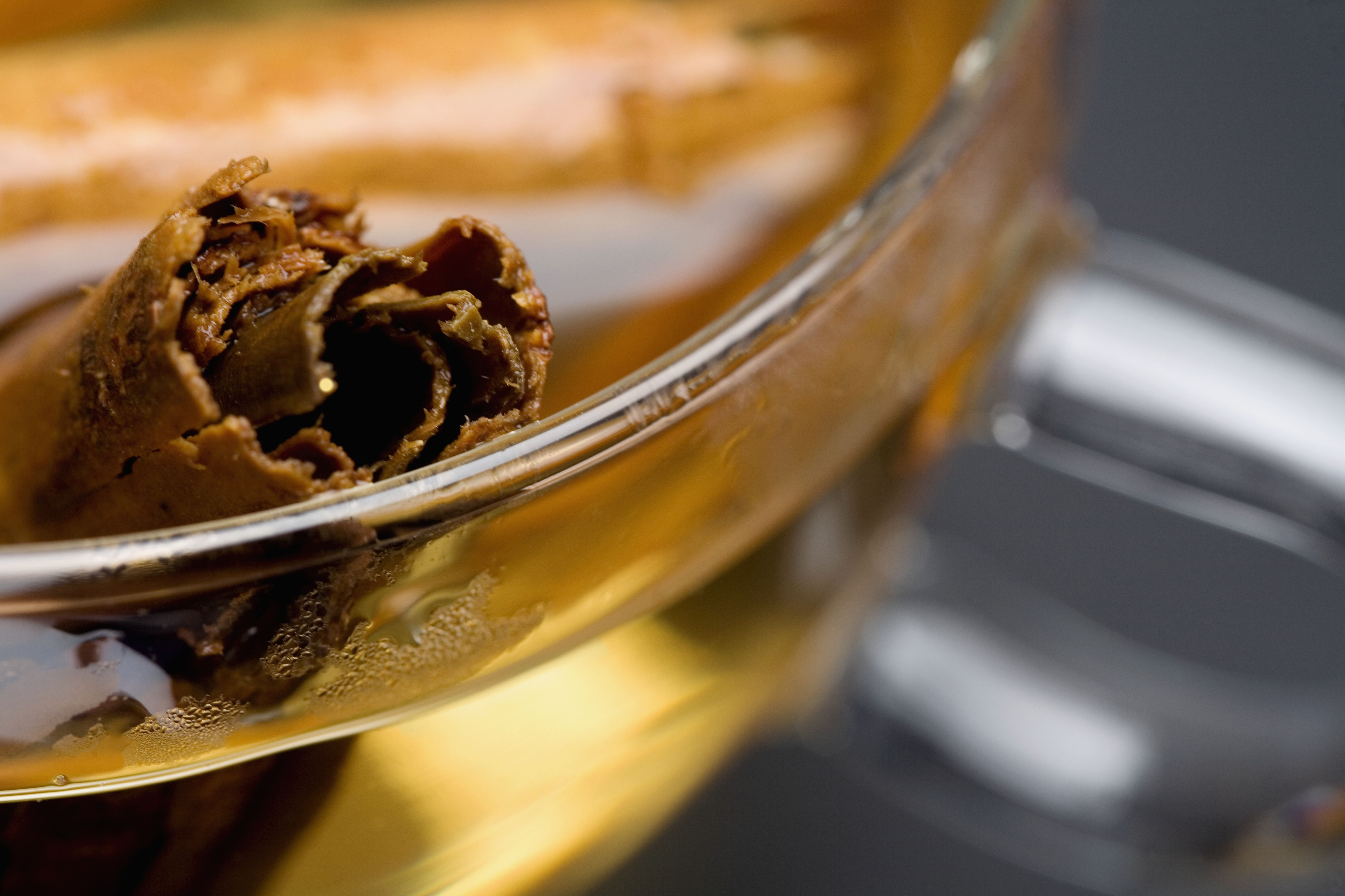 Close-up of a cinnamon stick in a bowl of cider