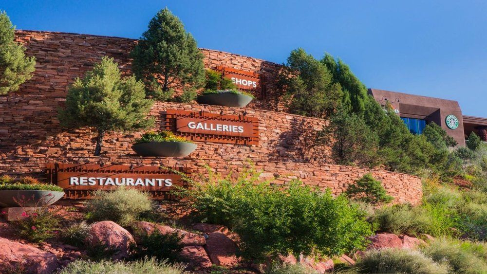 series of three red rock stone walls each with a sign. From top to bottom the signs read