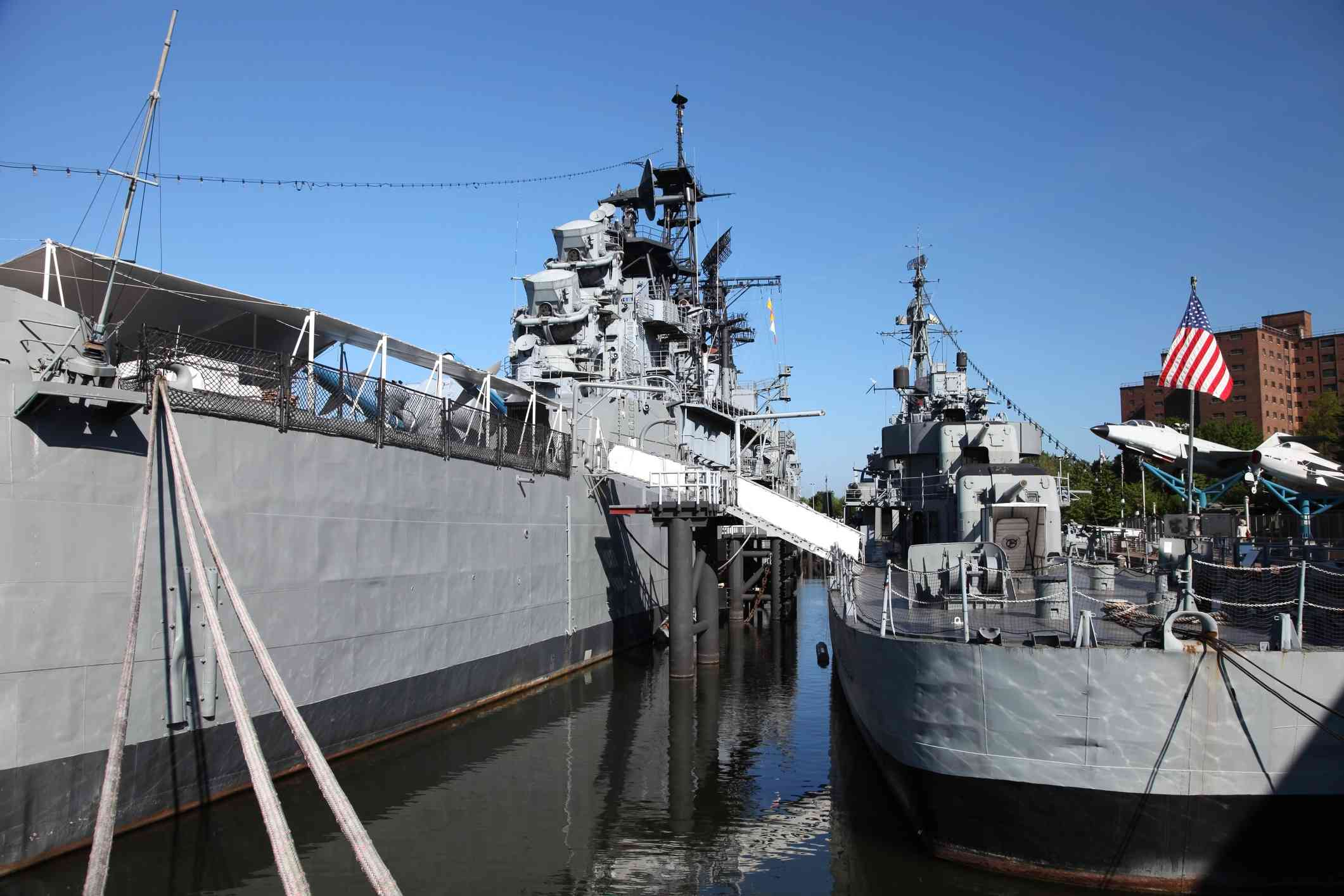 grey naval ship docked near shore with blue sky and US flag