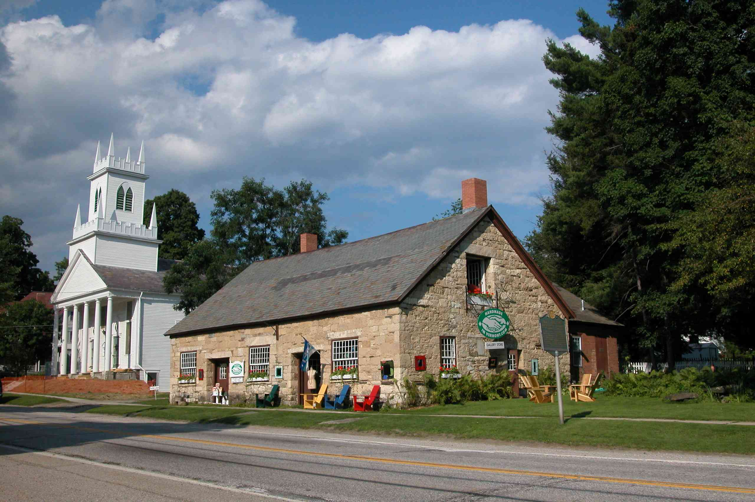 Stone general store on a street with a white buildings in Wallingford, Vermont