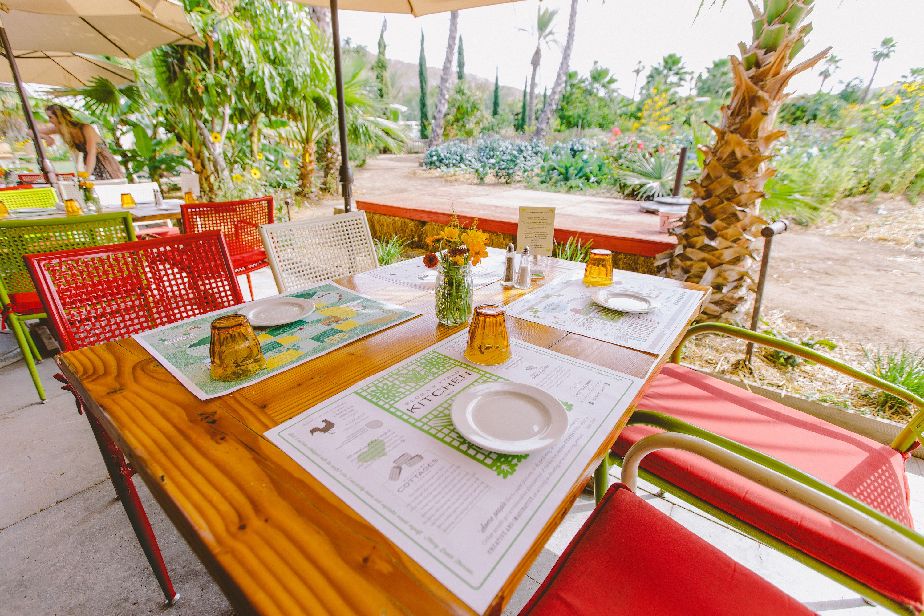 A set table with a garden in the background at Flora Farms in Cabo San Lucas