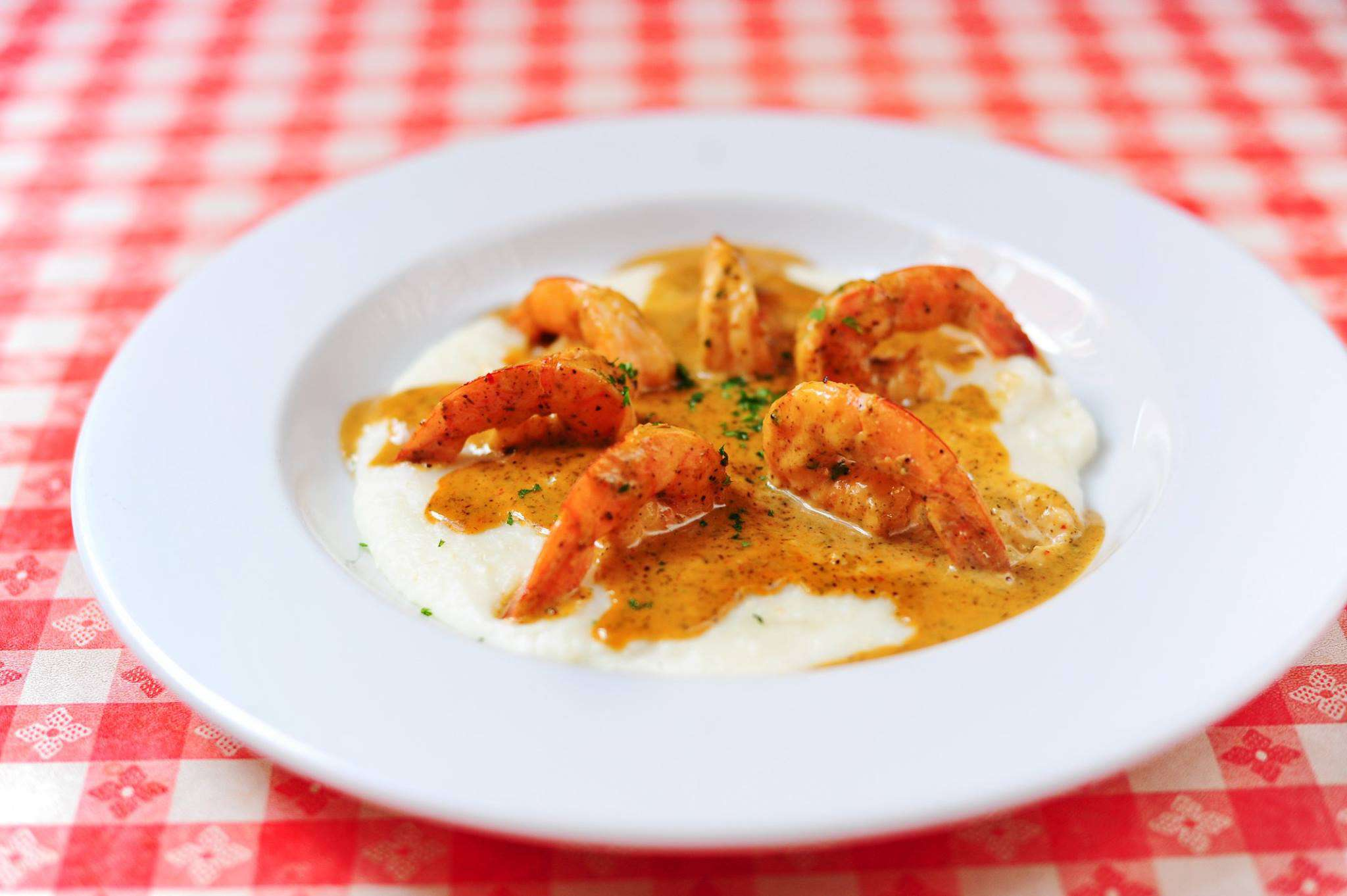 Six shrimp placed in a circle on top of grits covered in a creole sauce