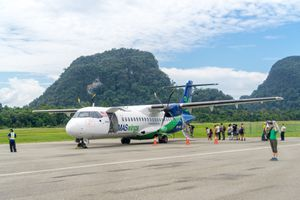 passengers waiting to board an airplane on the tarmac with a tree-covered mountain in the background