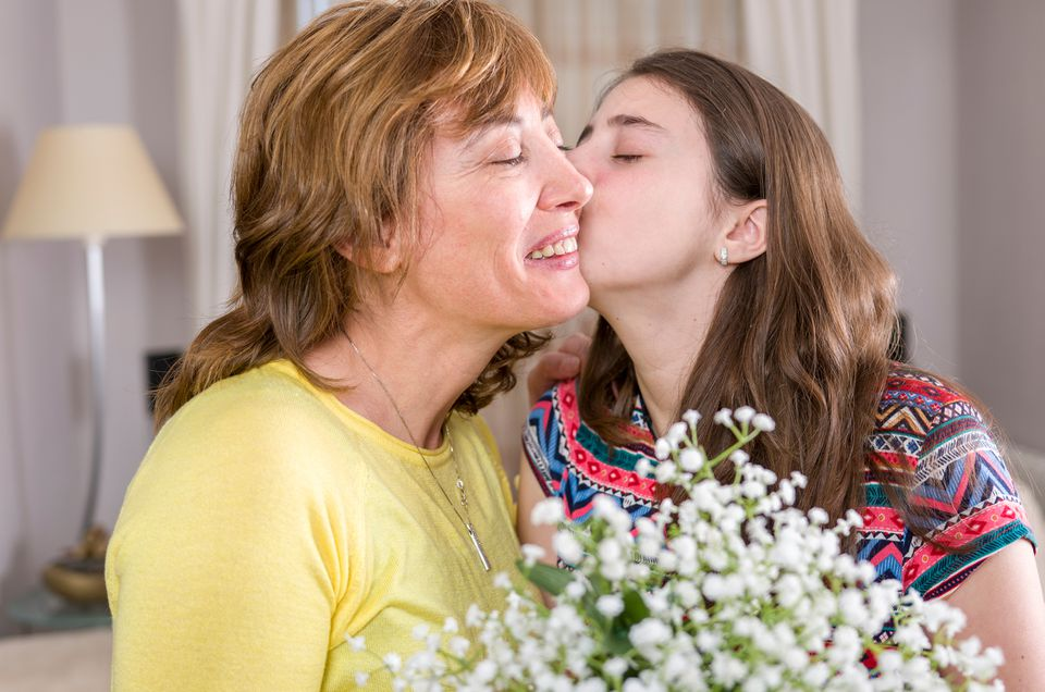 Girl kissing her mother with flowers