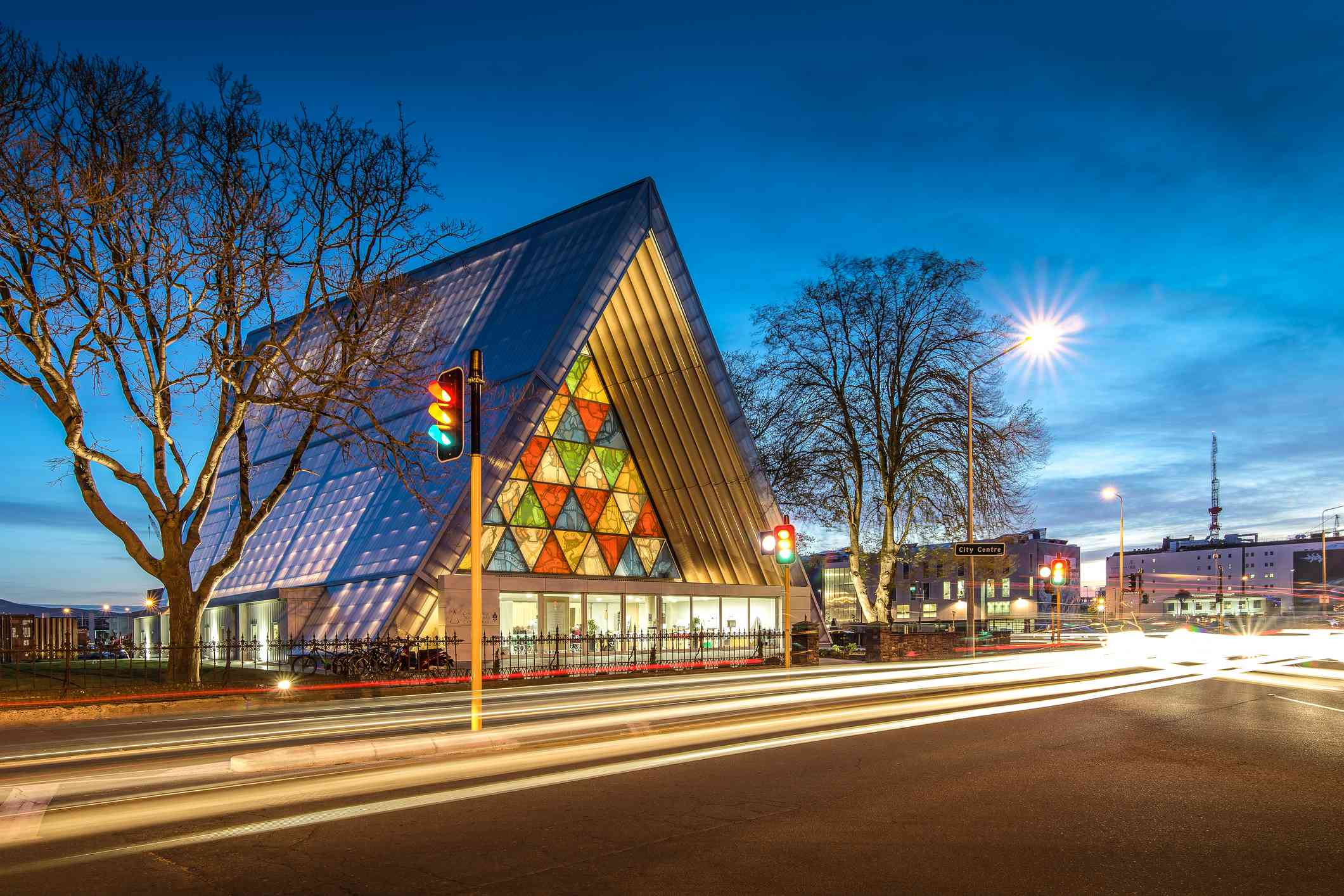 triangular church building with colorful windows and car lights at dusk