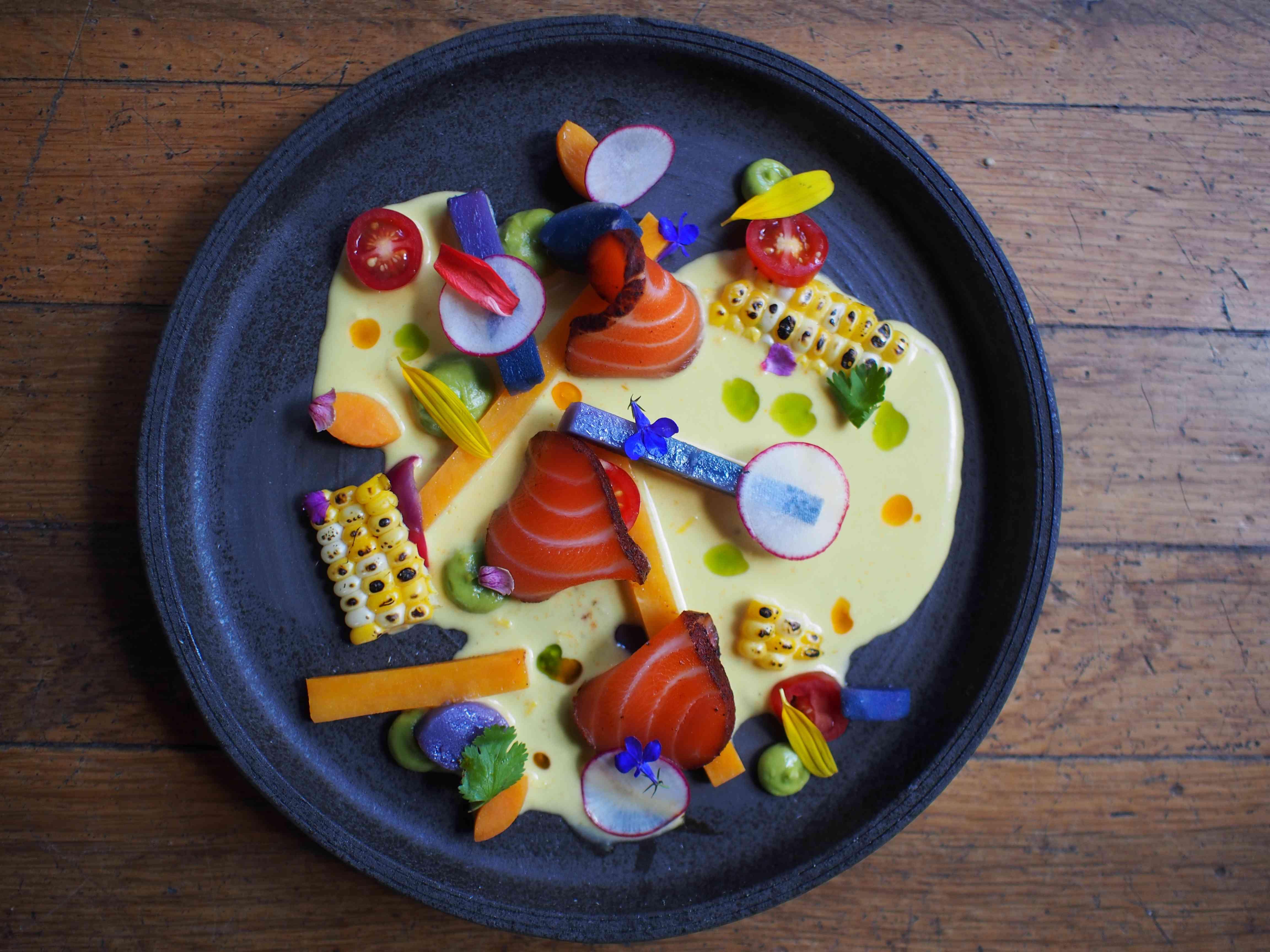 Dispuso artísticamente el sashimi de salmón en un plato circular negro con maíz carbonizado, palitos de zanahoria, tomates cherry, papas moradas y rábano en rodajas finas con una salsa cremosa