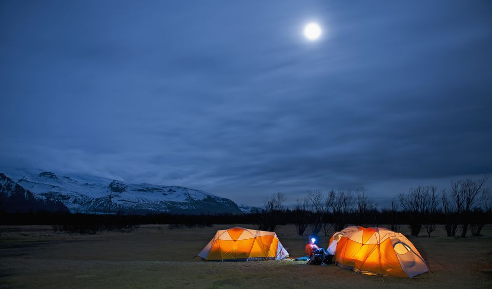 Mature woman sitting outside tent at night, Skaftafell, Vatnajokull National park, Iceland
