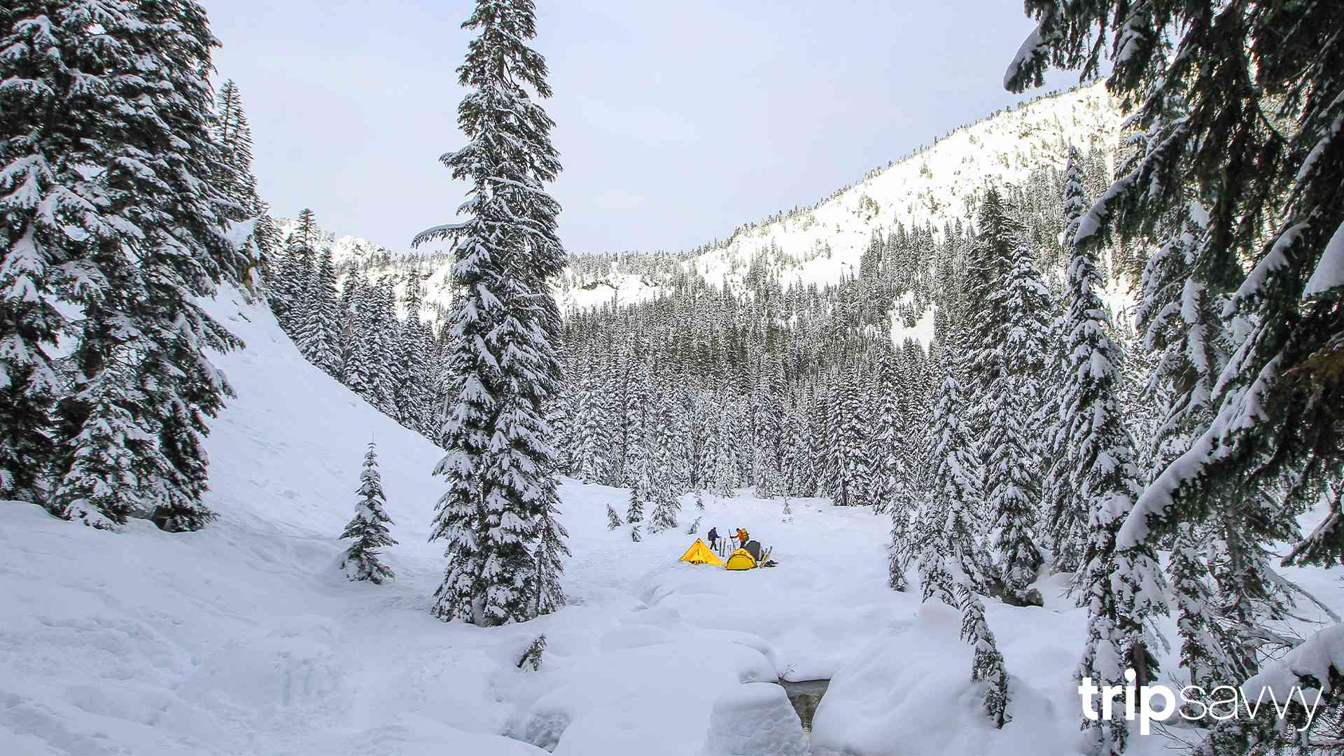Two hikers setting up camp in the snowy Cascade Mountains