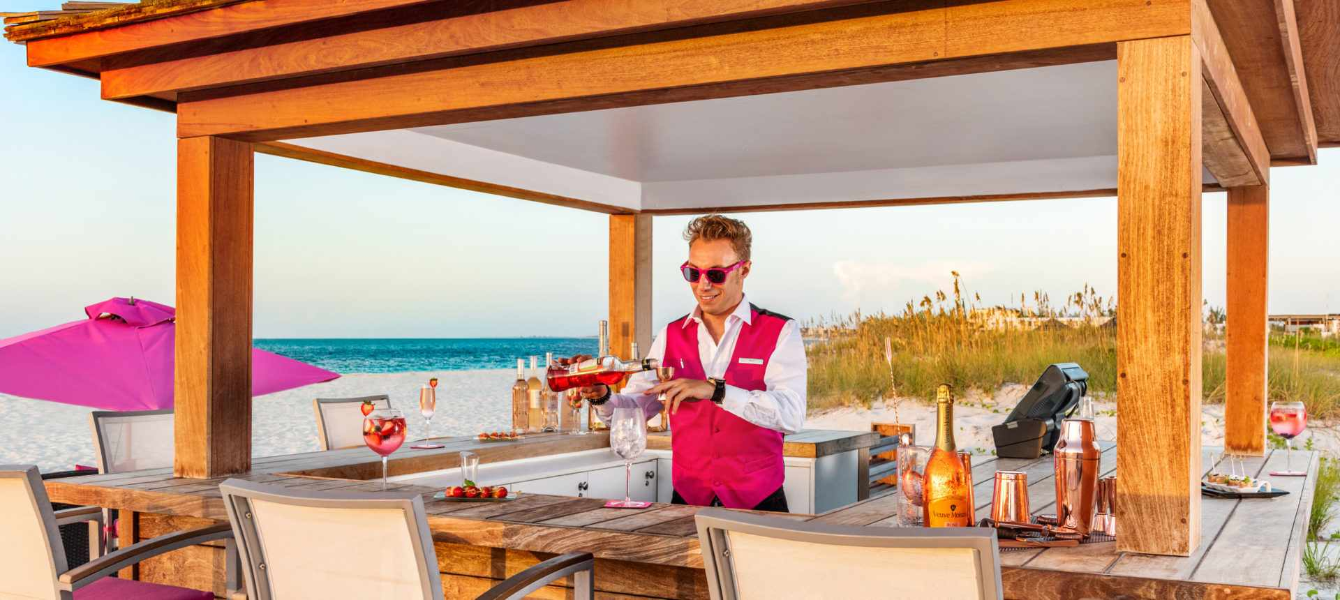 bartender in a pink vest and sunglasses mixing a drink