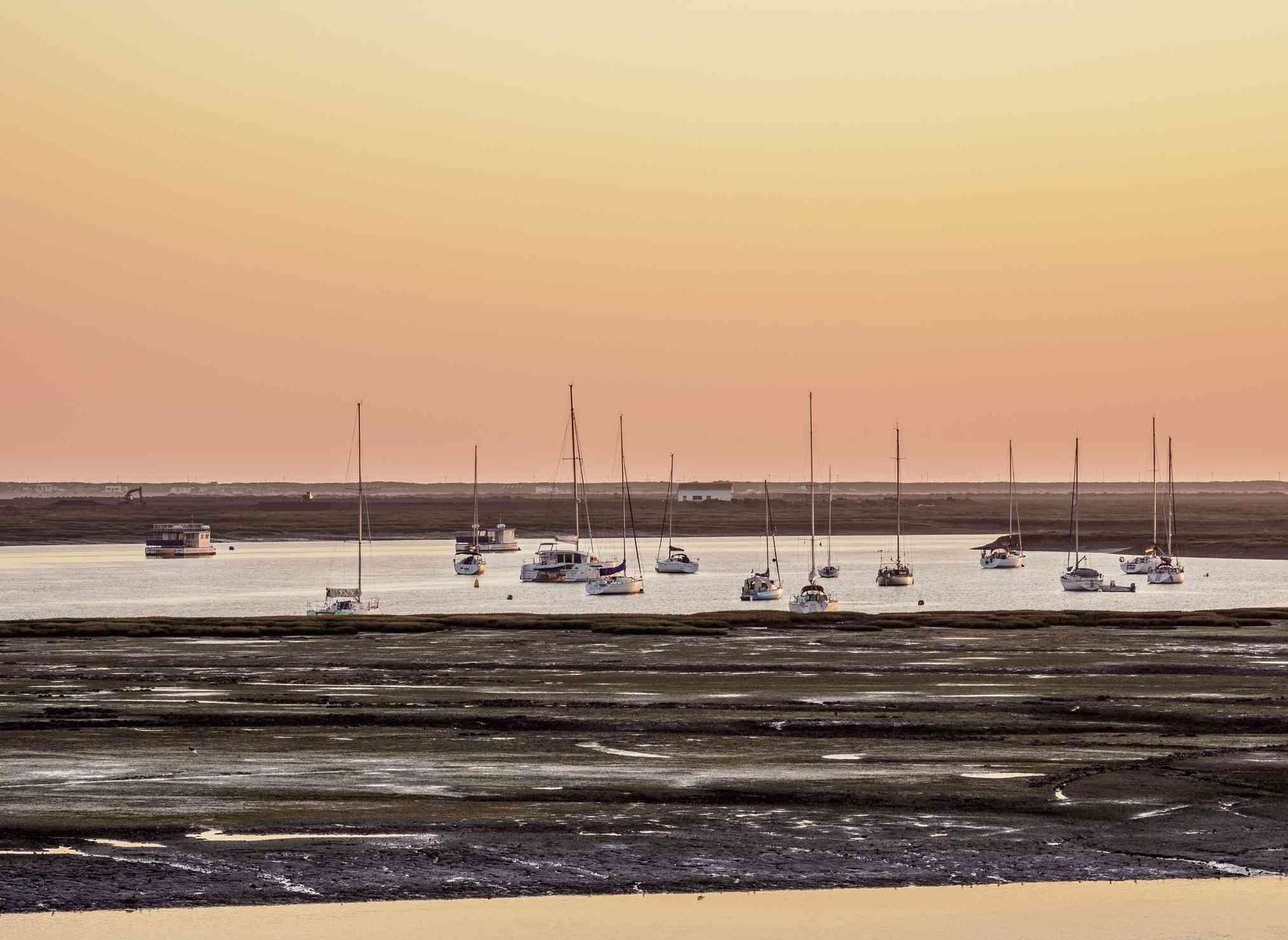Sailboats Moored In Sea Against Orange Sky