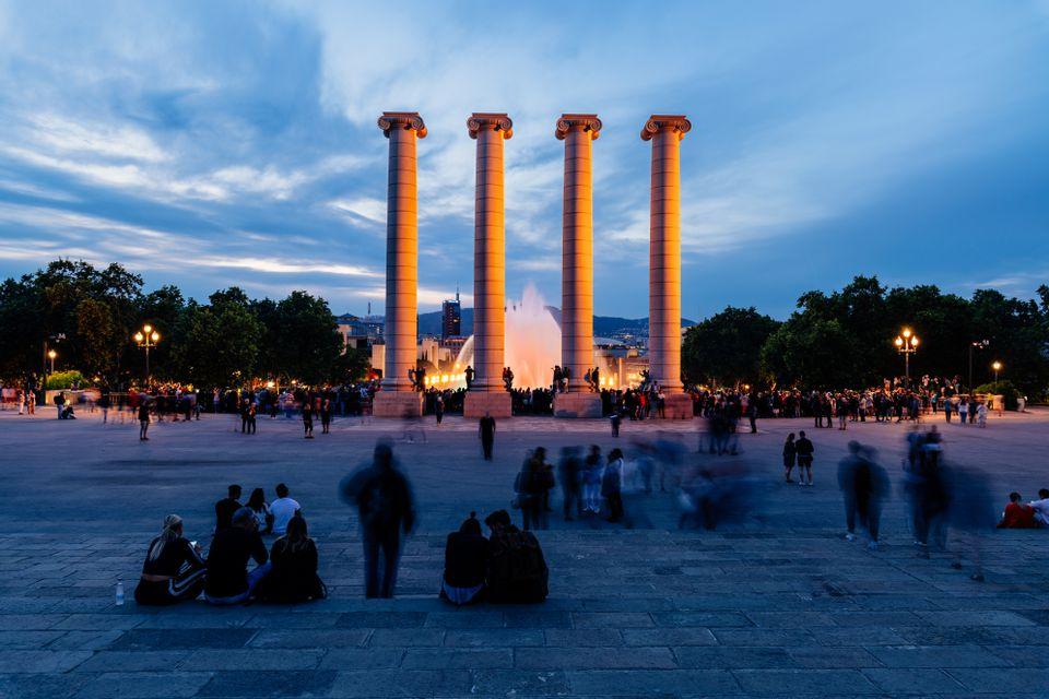 Columnas romanas frente a un espectáculo de fuentes al atardecer
