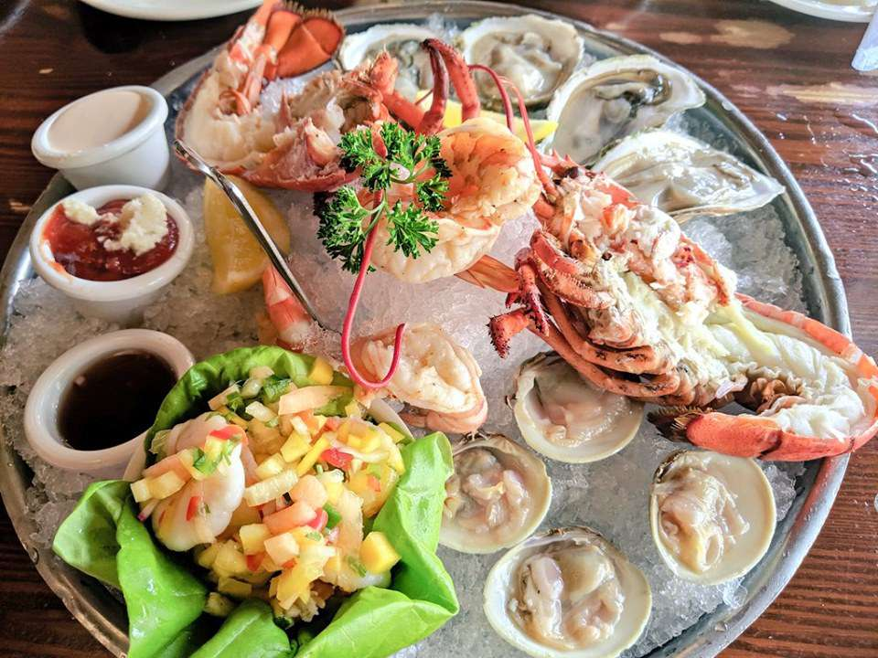 large sliver tray with an assortment of seafood on ice including: 4 oysters on the half shell, ceviche wrapped in a lettuce leave, two lobster halves, four clams and a few shrimp with cocktail sauce, a dark brown sauce and a creamy sauce on the side