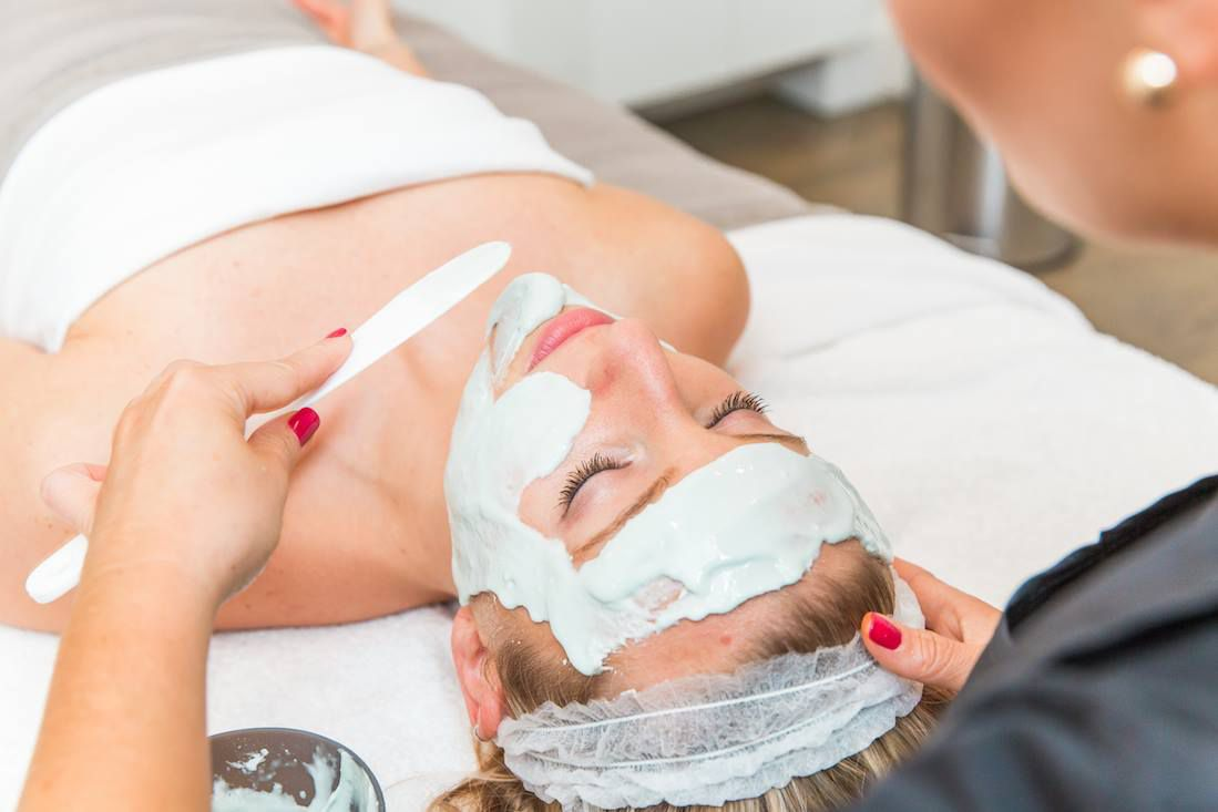 Spa technician applying a rubberized face mask to a caucasian woman's face with a wooden spatula Balans Organic Spa