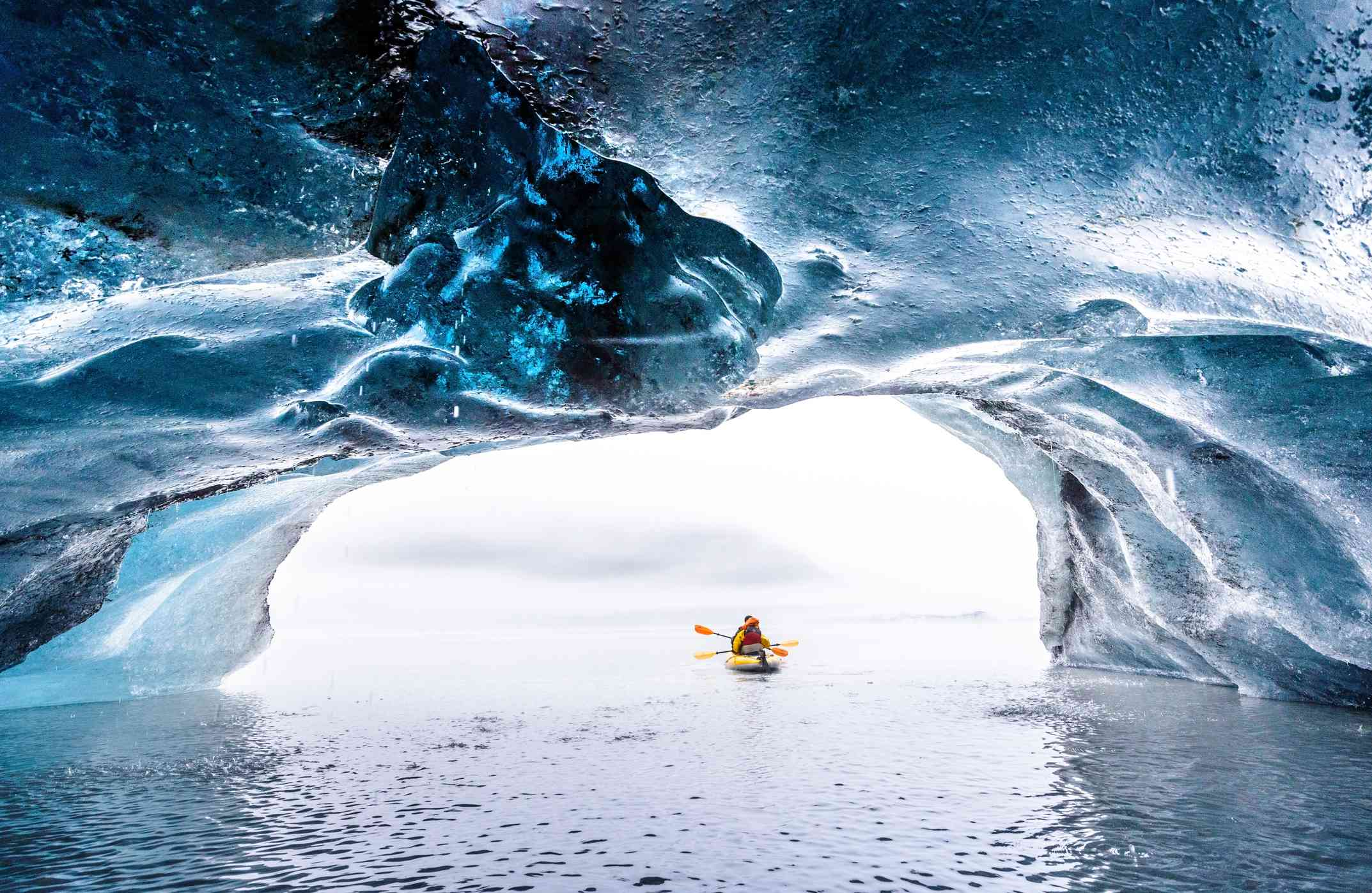 view of kayakers going toward an ice cave, taken from inside the cave