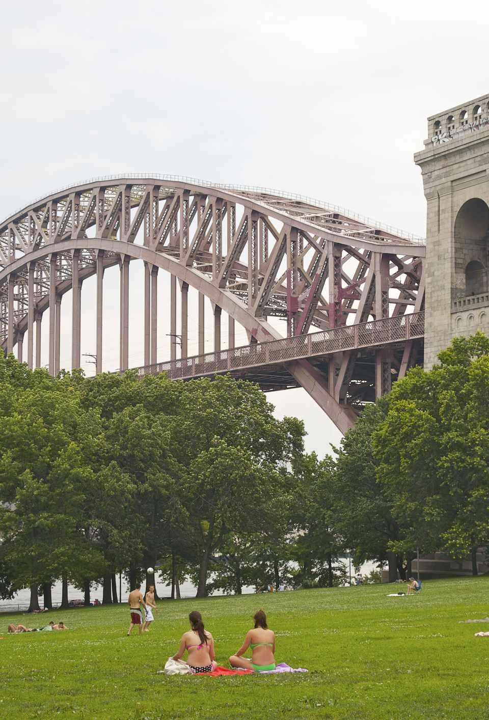People in Astoria Park beneath Hell Gate Bridge, Astoria, Queens, NY