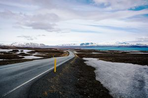 The ring road curving around the coast of Iceland with snow capped mountains in the back