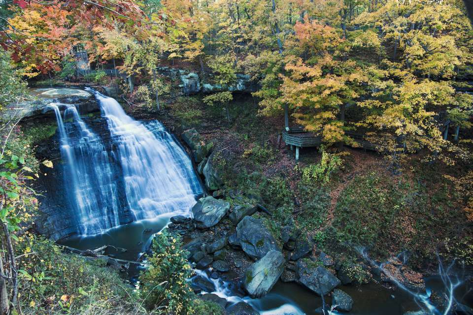 Small waterfalls Cuyahoga Valley national park with yellow and red autumn trees on either side