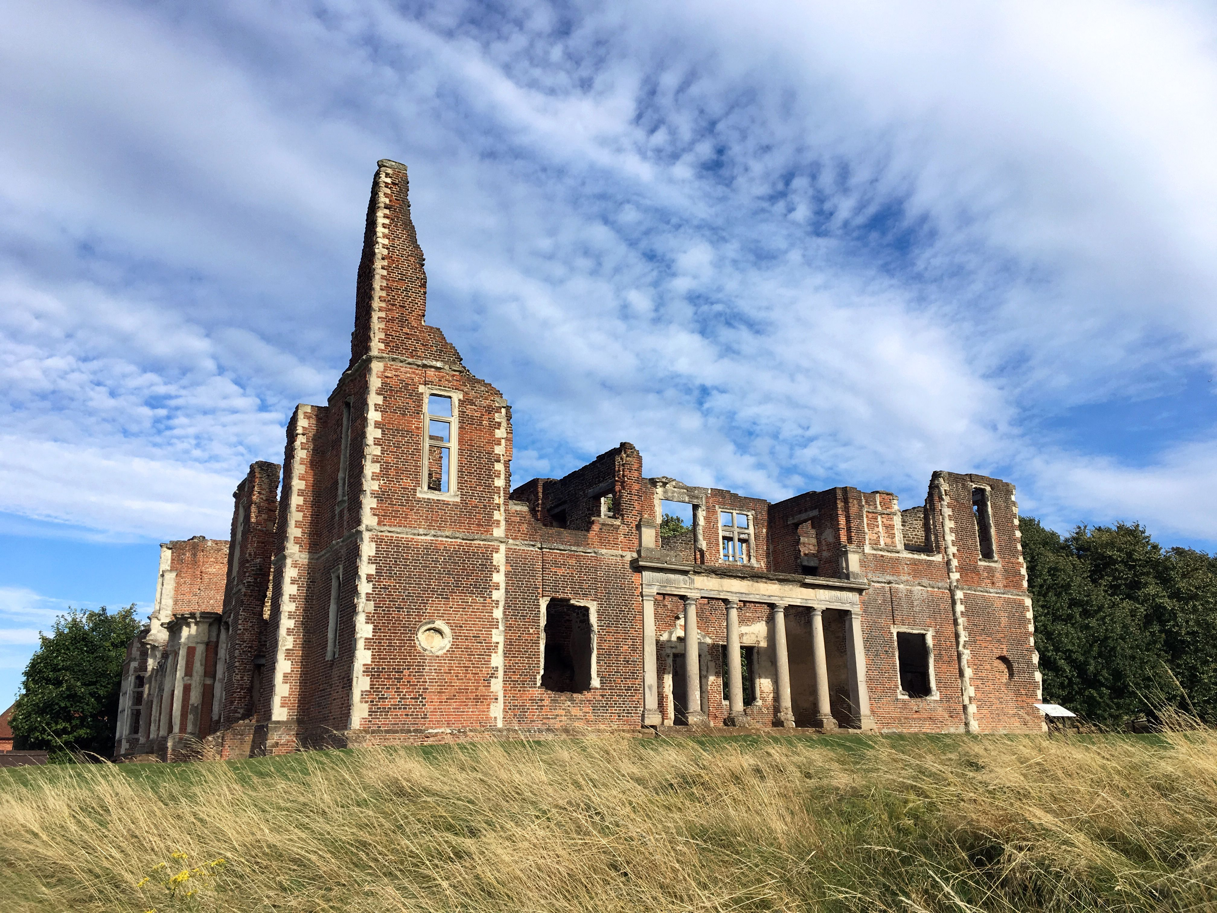 Old Ruins Of Houghton House On Grassy Field Against Sky