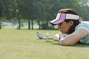 Woman lying on grass looking at golf ball