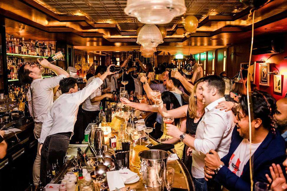 A rowdy bar with drinks flowing and people having fun