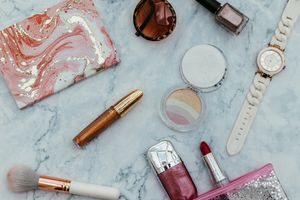 Makeup bag on table with beauty products and sunglasses