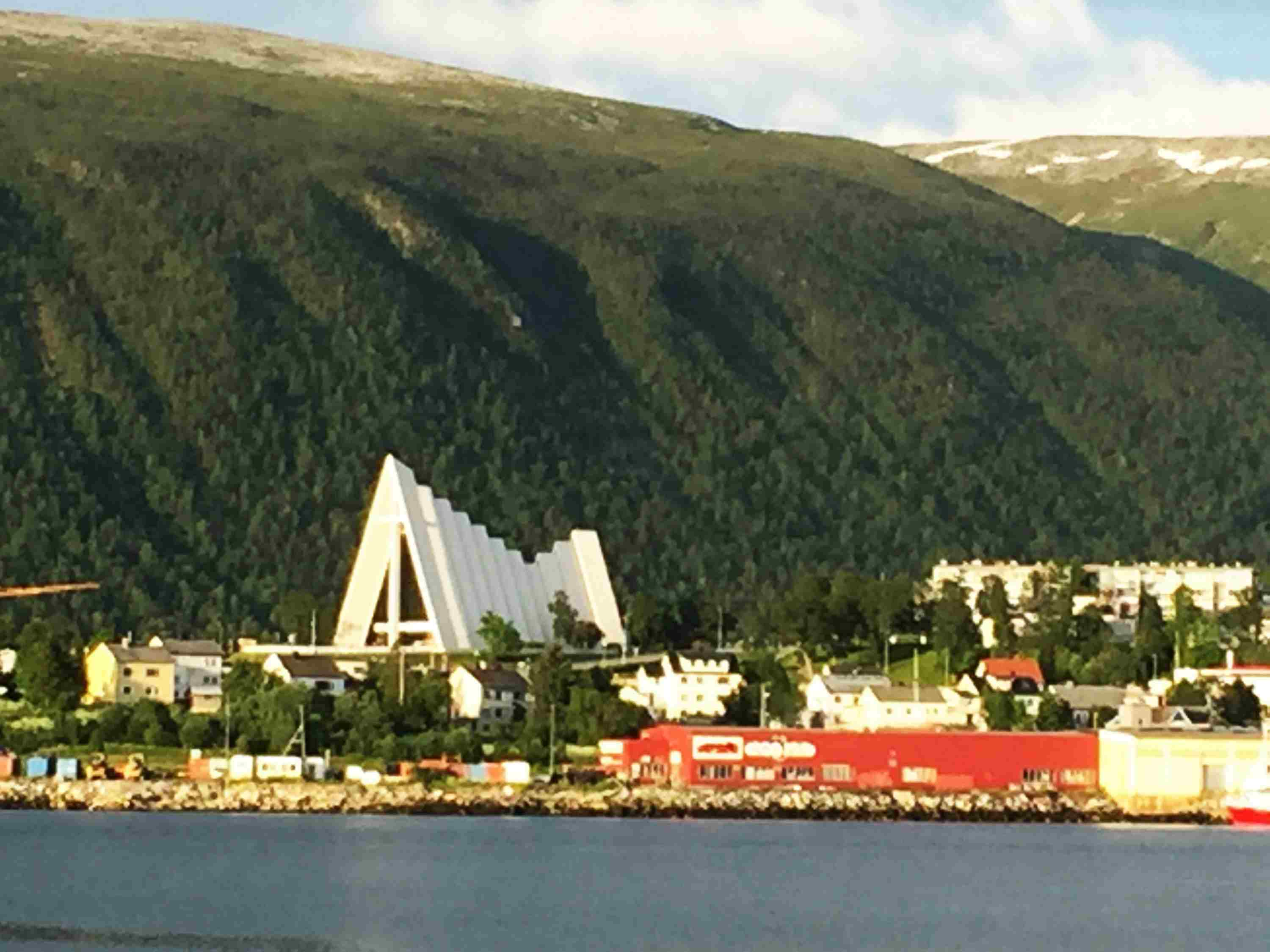 Tall, white cathedral next to water and green mountains