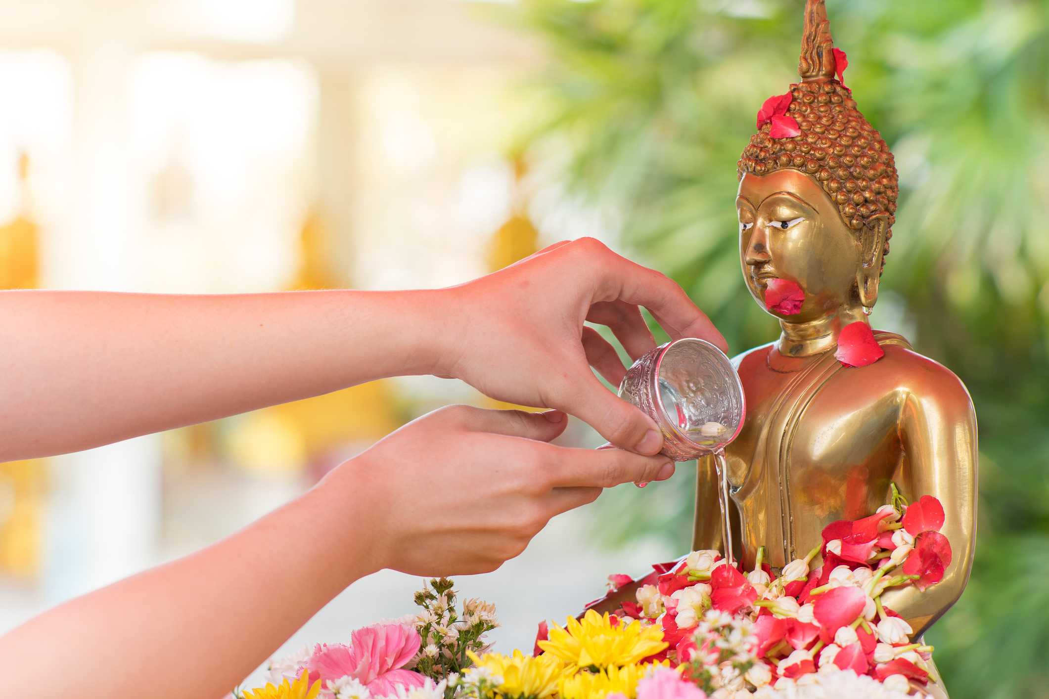 Devotee pours water on Buddha image for Songkran