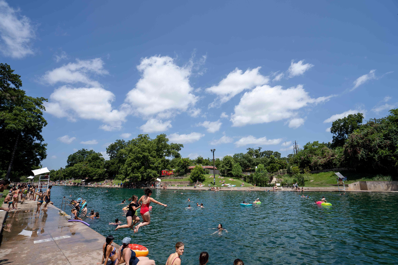 Dos chicas saltando al agua en Barton Springs