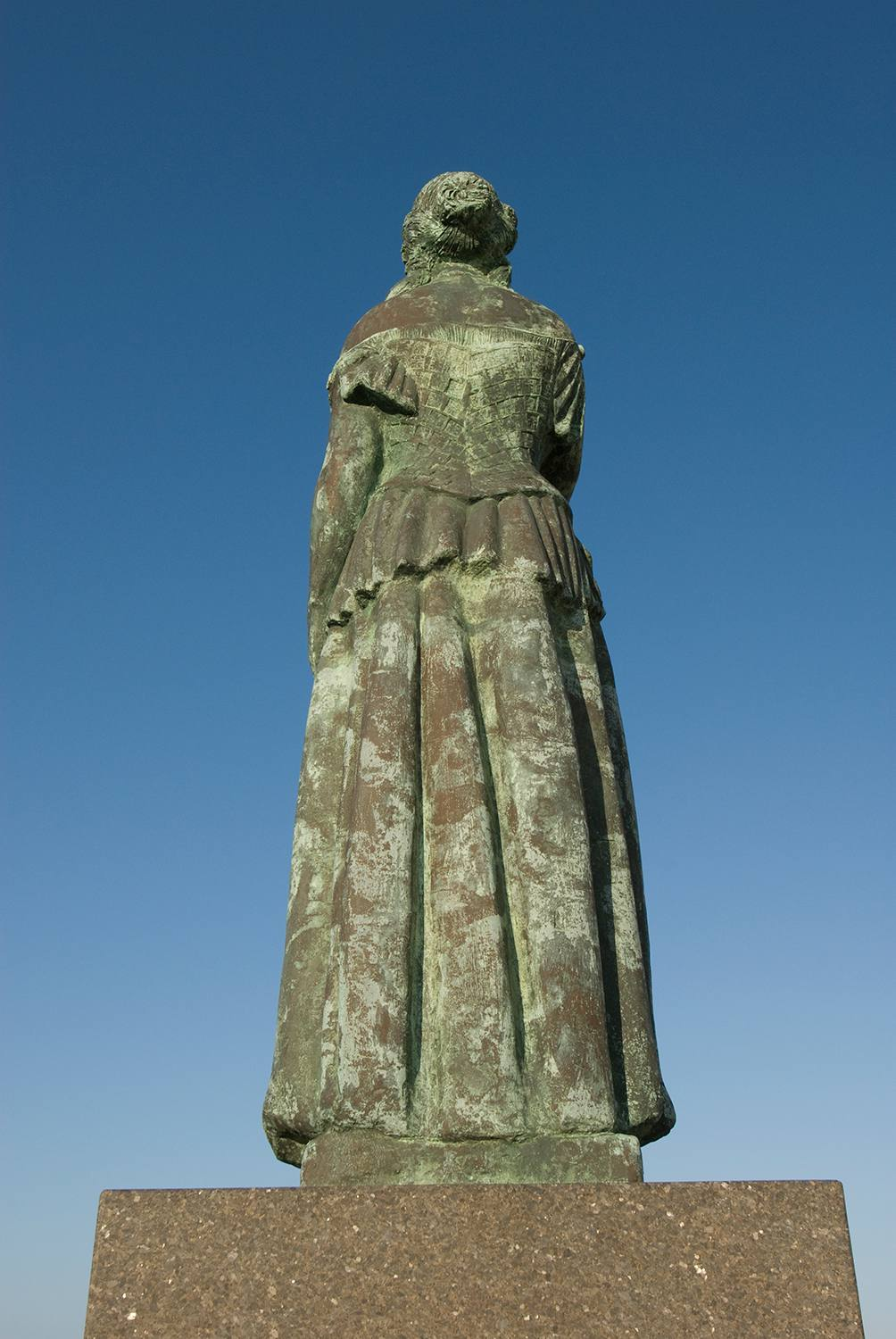Back view of Norwegian Lady Statue, weathered green with colonial dress and hair pulled back into a bun, in Virginia Beach, pointed in the direction of Moss, Norway.