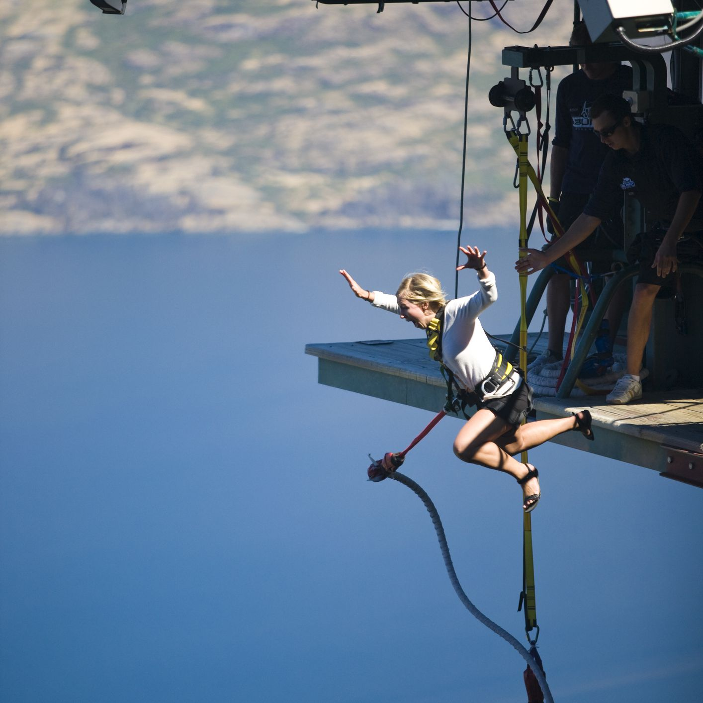 blonde woman jumping off platform with bungee cord attached and blue lake below