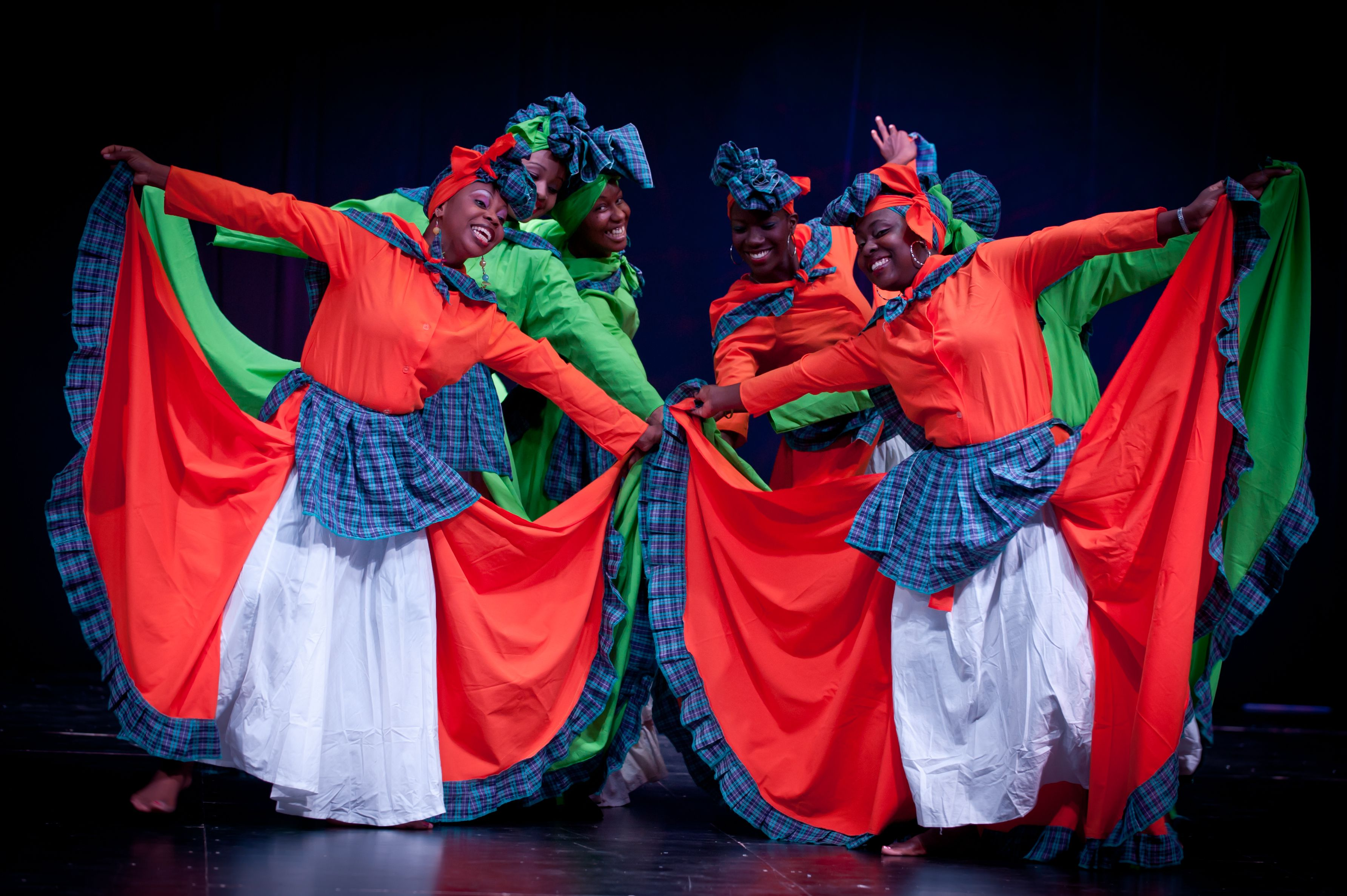 Six dancers in red and and green costumes dancing on stage at the Spice basket