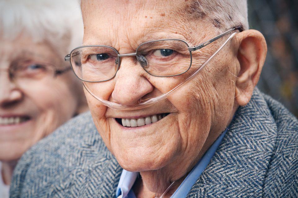 Hombre mayor sonriente con tubo de oxígeno