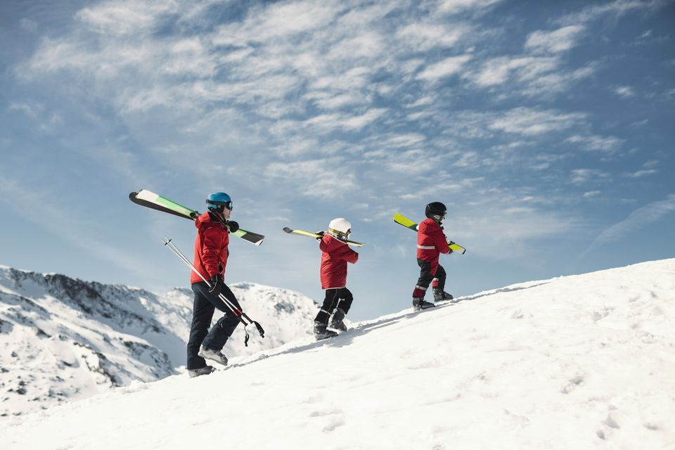 Family walking up a ski slope