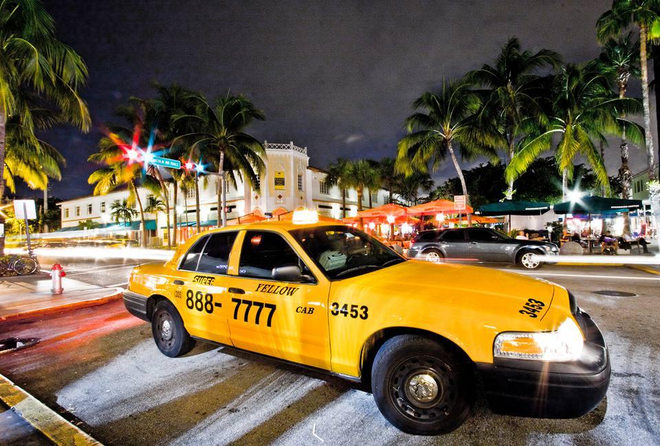 Fotografía nocturna de un taxi amarillo estacionado en Lincoln Road en Miami Beach.