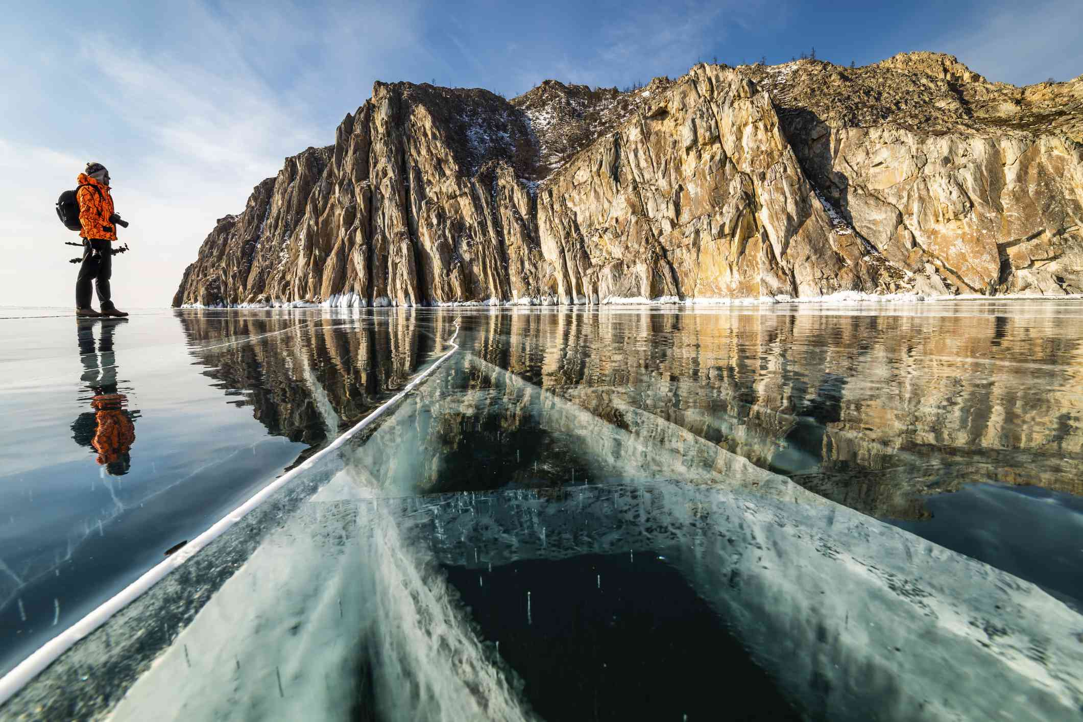 Photographer on the background of a rocky cape on Lake Baikal in winter