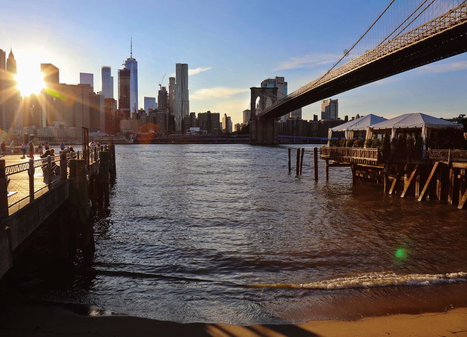 A view of the brooklyn bridge from the shore with a view of the Manhattan skyline