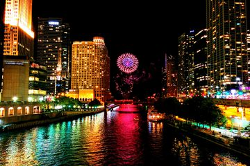 Chicago River Amidst Illuminated Buildings With Firework Display At Night