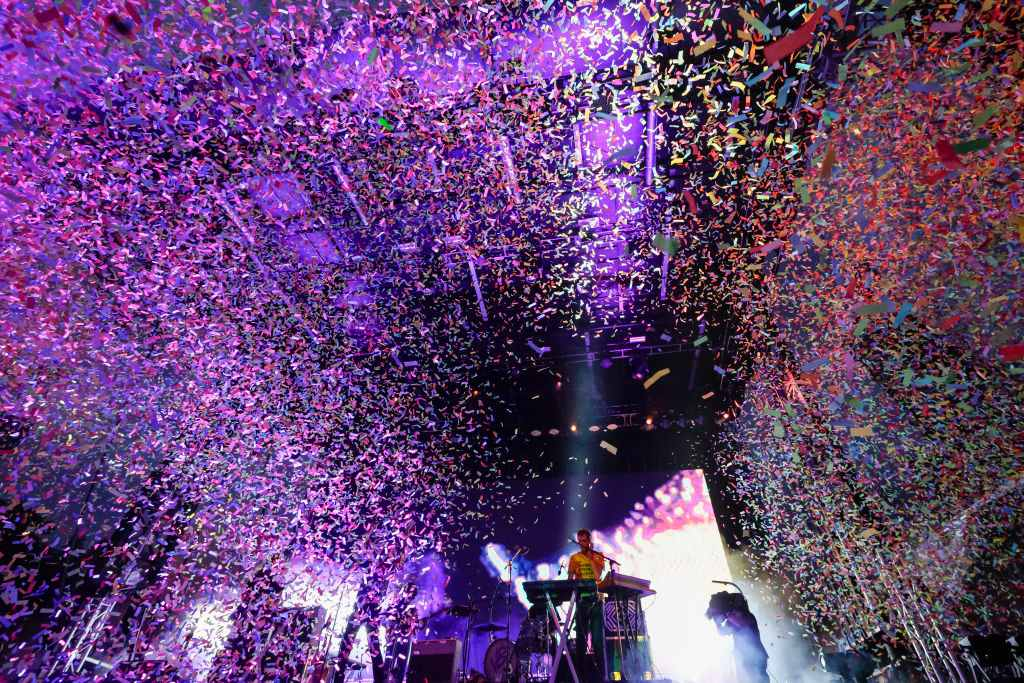 DJ performing in union park, chicago with rainbow confetti falling