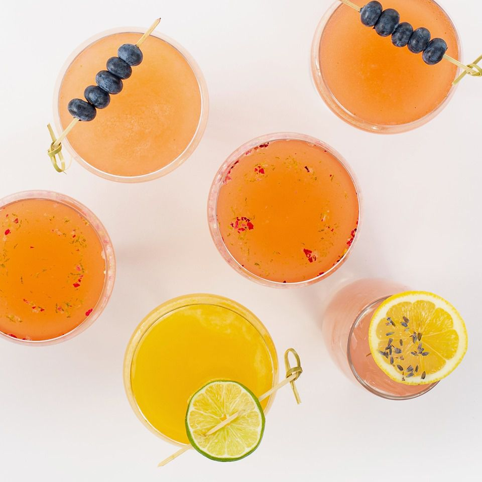 overhead shot of six orange-colored drinks, two with a skwere of blue berries resting on top, two with dried flowers sprinkled over the drink, one with a lime garnish and one with a lemon garnish