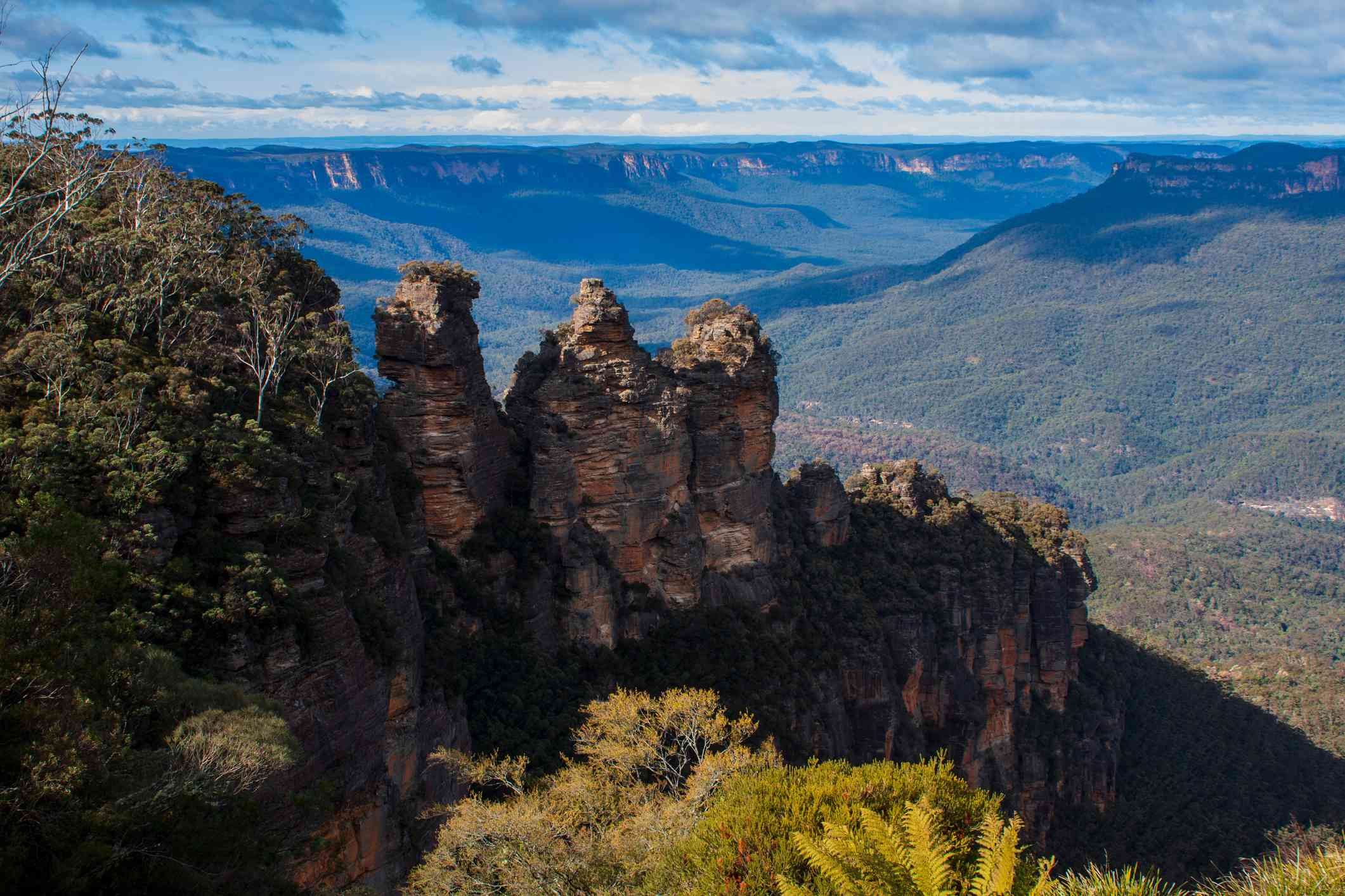 Three Sisters rock formation from Echo Point lookout with the Blue Mountains in background